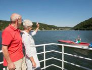 A couple waving from a passenger boat on the Diemelsee